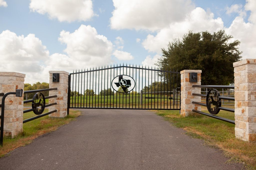 custom gate with stone columns, and pipe fencing with dog artwork