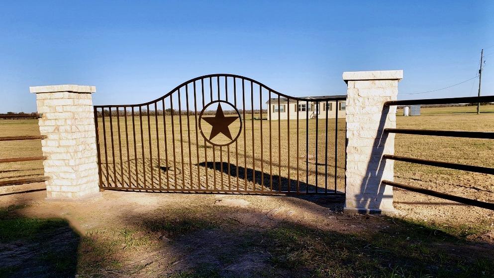 texas star themed gate with stone columns and pipe iron fencing